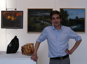 Man with shirt sleeves rolled up beside two small sculptures wtih three medium sized paintings on the wall behind him