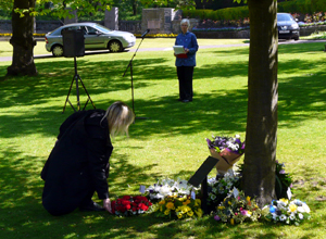 Woman in black crouching to lay a wreath among others at the foot of the memorial tree