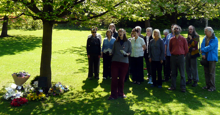 Group of a dozen people singing under a tree in Princes St Gardens, which has bouquets of flowers laid around it