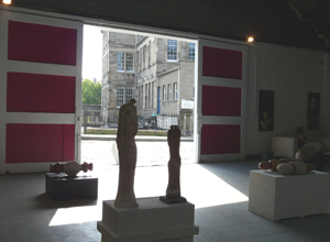 View of some sculptures looking out through open shutters to St Mary's Primary school