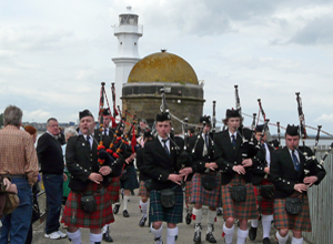 A dozen pipers with  Newhaven  Lighthouse in the background