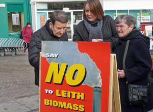 "Three people look at an A Board saying ""SAY NO TO LEITH BIOMASS"