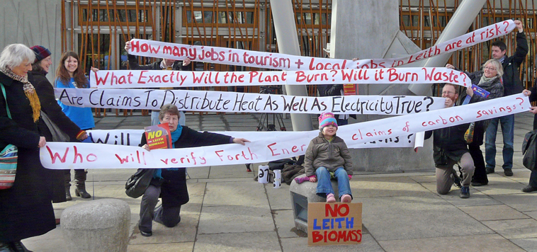 "Zoe sits in front of banners asking questions about the Leith Biomass Plant such as ""Who will verify Forth Port' claim of carbon savings?"