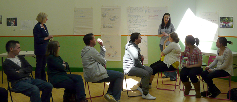 A young woman standing by flip chart pages listens to a group of young people as Maggie Havergal in a casual blue suit watches on