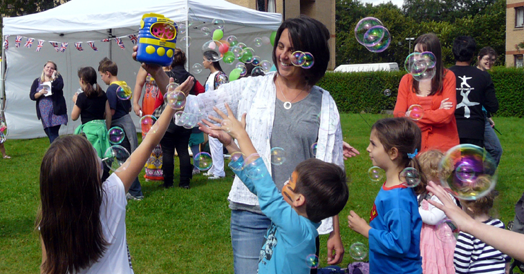 Smiling woman holds up bubbling bubble machine as children reach up to the the bubbles