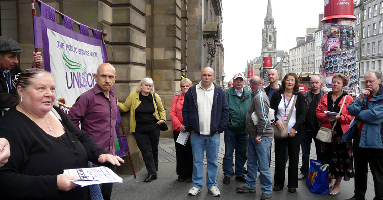 speaking to a group outside the City Chambers with a view of the High St in the background