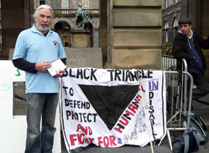 Bearded man in a sky  blue rugby shirt, stands beside a banner: BLACK TRIANGLE TO DEFEND PROTECT AND FIGHT FOR HUMANITY IN DISABILITY