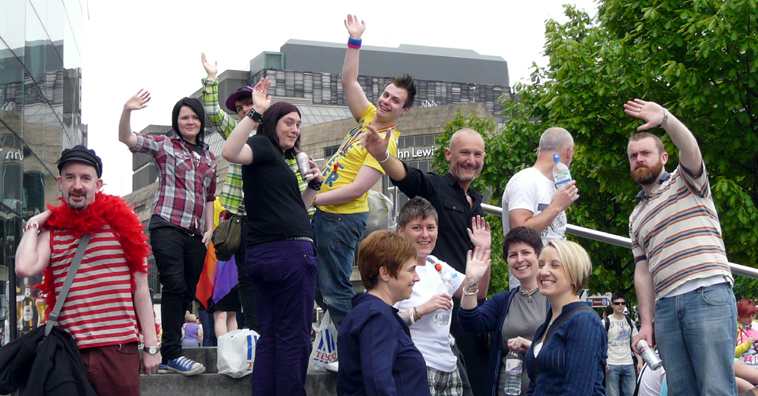 Groups of people waving, standing on the steps of the Omni Centre, with the St James Centre in the background