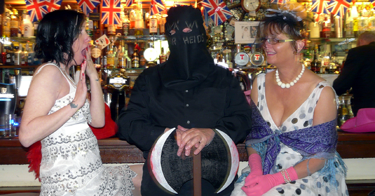 Two women in white dresses sit at a bar staring in horror and bemusement at a man dressed in black as an Executioner resting his hands on an axe