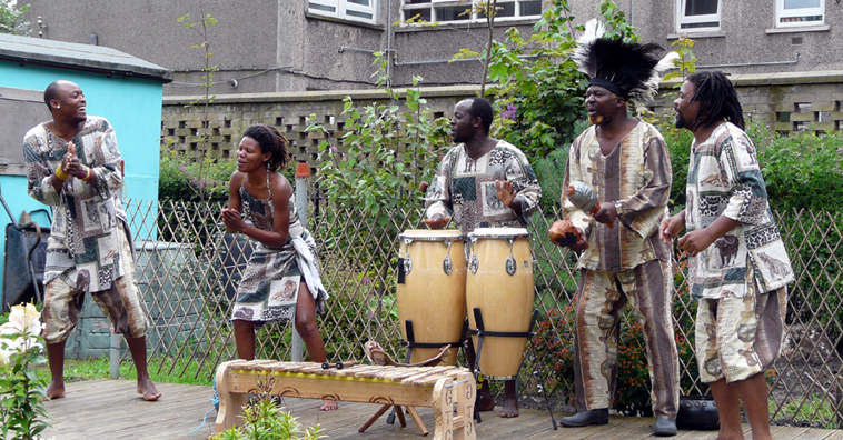 Grass Roots in African costume performing in Redbraes Garden with flats in the background