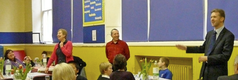 The three Councillors stand to speak to the school in the gym hall, with Mrs Thomson and pupils seated at dining tables