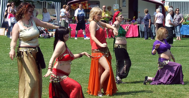 Five women belly dancing in line in various poses