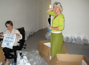 Jane Frere in olive green cottons smiling as a seated volunteer puts figures in a Scotmid bag
