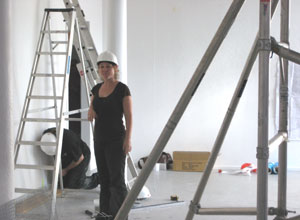 Woman in a white hard hat, standing between a step ladder and the foot of a scaffolding rig