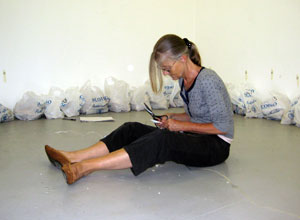 Woman sitting on the floor with Scotmid bags lined up along the wall.
